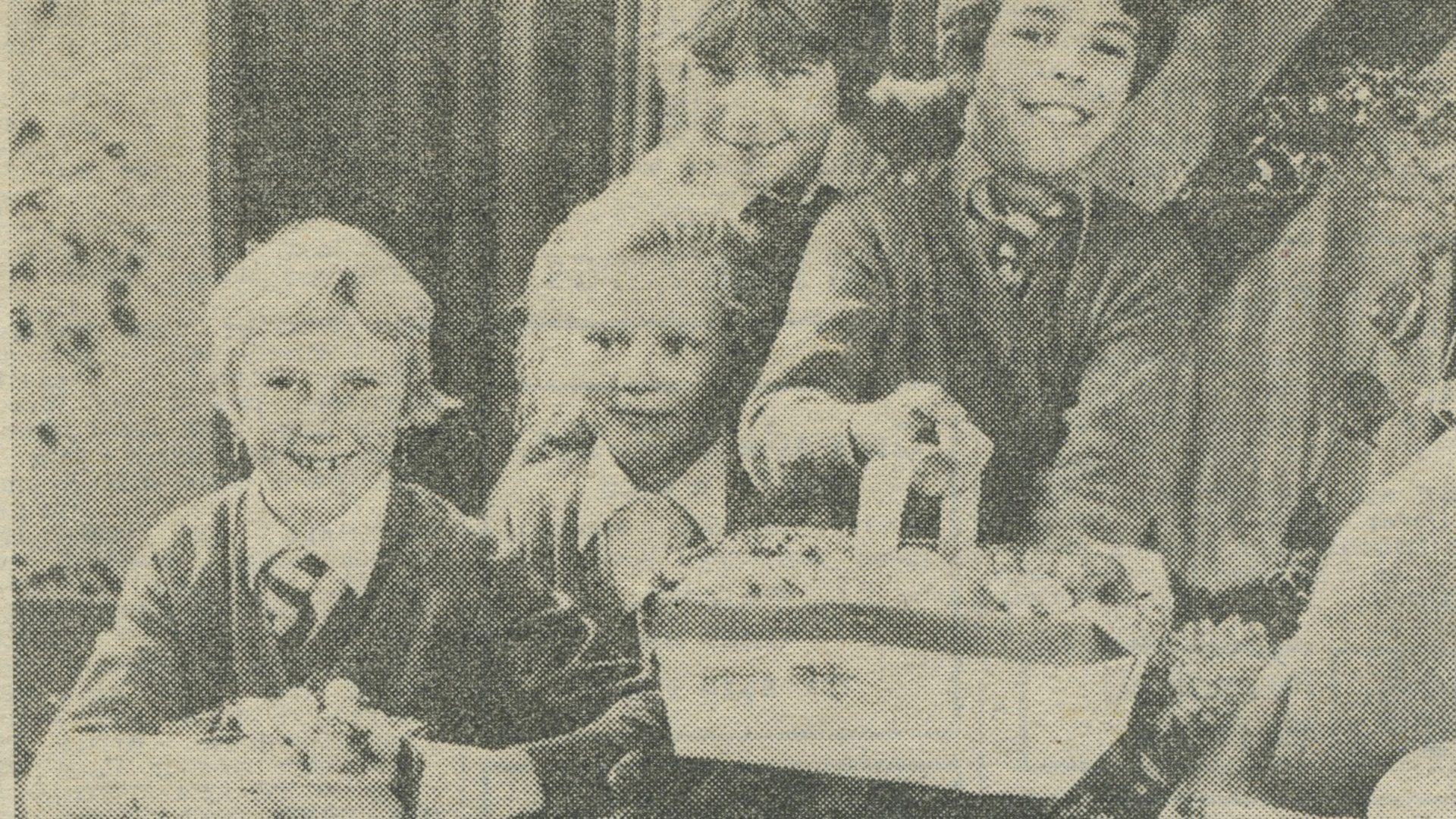 Press clipping of children donating harvest festival goods