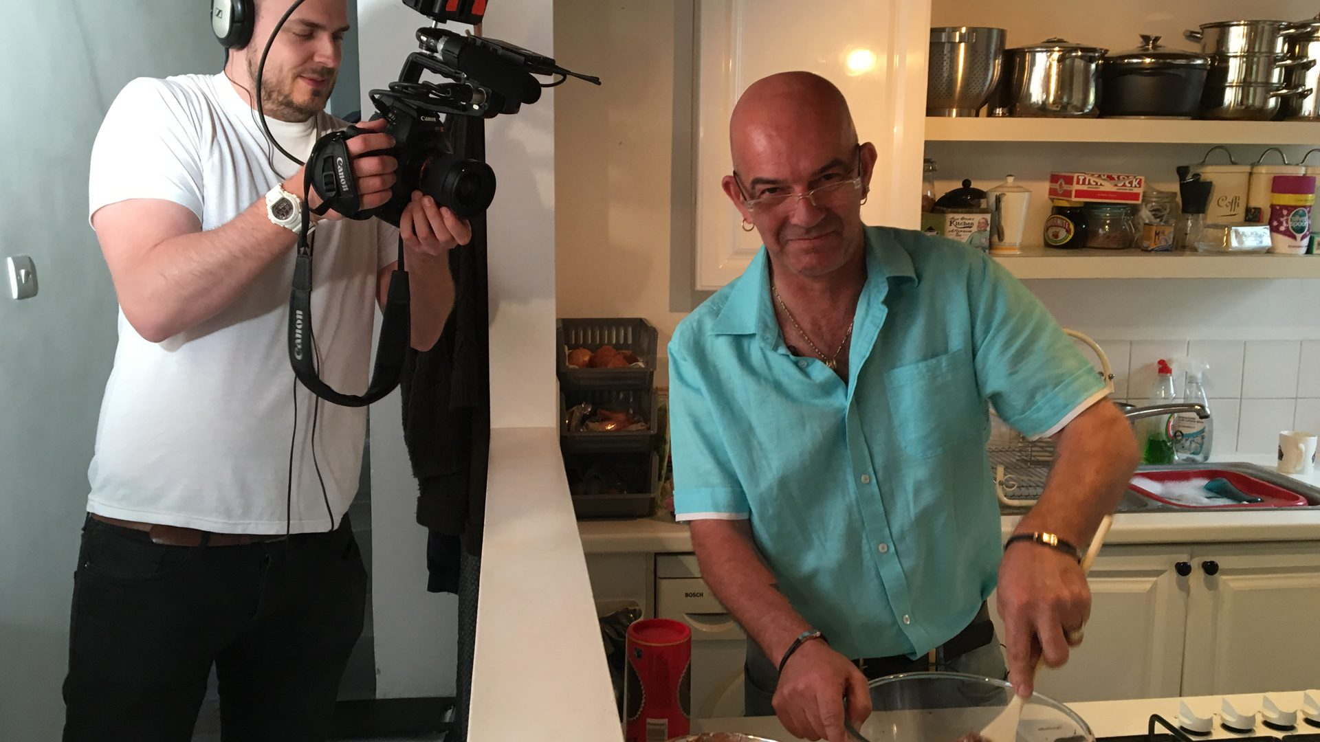 Man making cakes in kitchen whilst being filmed