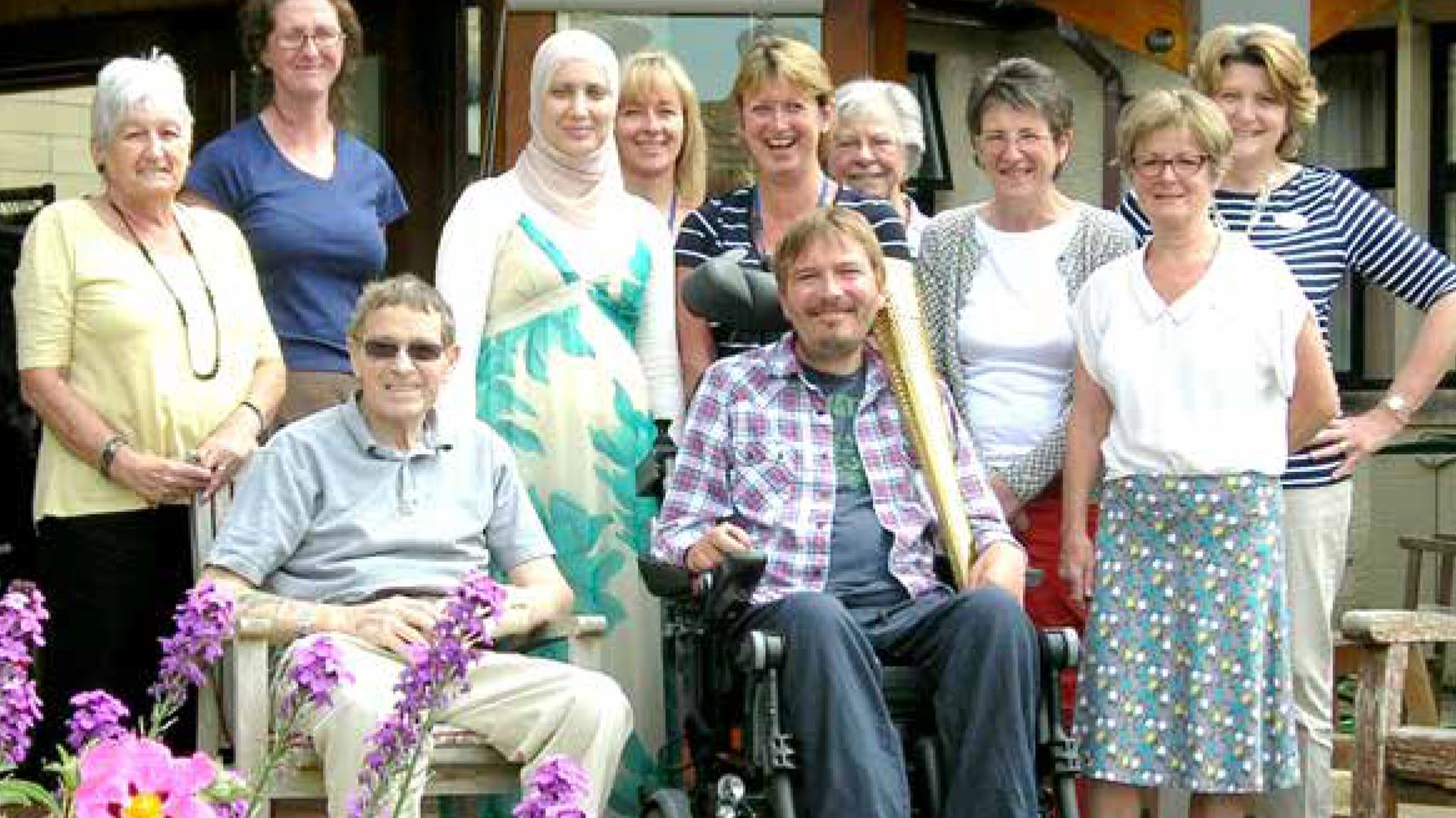 Group of patients and gent holding an Olympic Torch